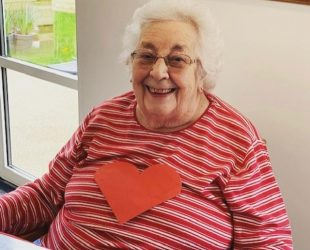 Abbeyfield Resident Smiling With Her Valentine's Heart Badge