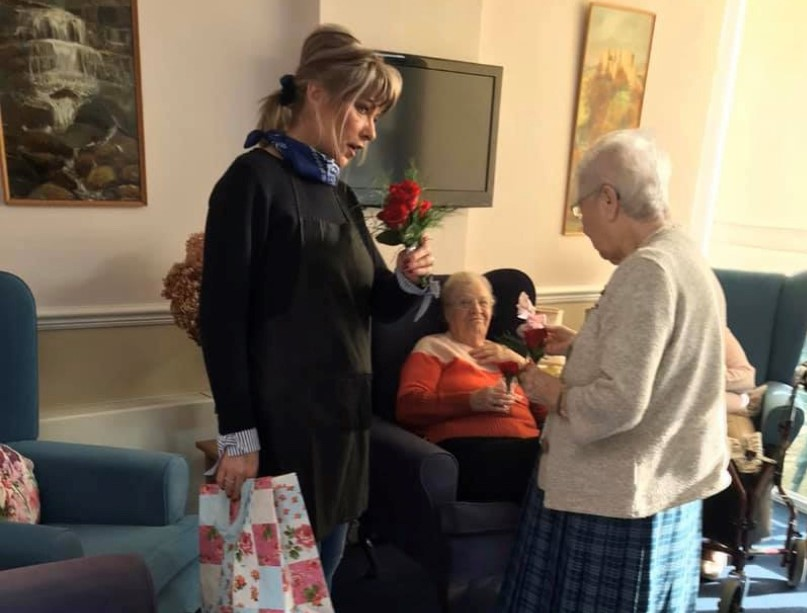 Pauline gives roses to residents at abbeyfield house
